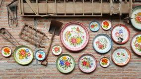 地方传统泰国金属盘子在砖墙上装饰 免版税库存照片