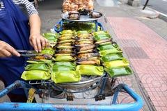 地方卖主做在香蕉叶子的泰国烤甜黏米饭在萨娜姆Pao,曼谷,泰国 免版税库存图片