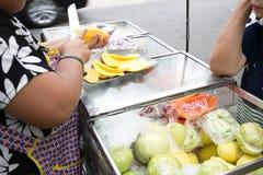 地方卖主切了成熟新鲜的芒果在Phra Athit路,曼谷,泰国 免版税库存图片