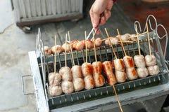 地方卖主厨师东北泰国样式肉香肠在Bangrak市场,曼谷,泰国上 免版税库存图片