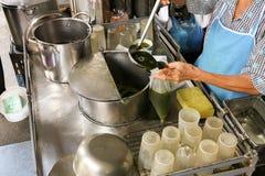 地方卖主组装亚洲pennywort汁液, Bai Bua Bok饮料在Talad Phu市场,曼谷,泰国上 图库摄影