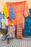 地方卖主在马拉喀什,摩洛哥提供在souks的纺织品 免版税库存图片
