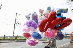 地方在大街, Samutprakarn,泰国的卖主出售五颜六色的气球 免版税库存图片