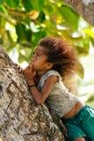 地方女孩坐一棵棕榈树在Lavena村庄,塔韦乌尼岛Isl 免版税库存图片