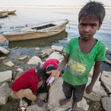 地方孩子在圣洁恒河的银行的沙子开掘发现硬币被投掷作为礼物对神由香客 免版税库存照片