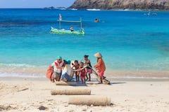 地方孩子帮助父母拖延传统渔夫小船 免版税图库摄影