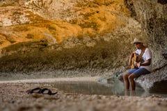 地方歌手歌曲作者演奏吉他和口琴在海滩 免版税库存照片