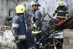 地方消防员帮助熄灭火在毁坏内部简陋小木屋房子的房子火期间 库存照片