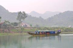 地方渔夫把游人带对在一条传统小船的旅行 免版税库存图片