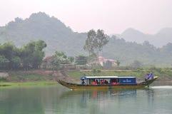 地方渔夫把游人带对在一条传统小船的旅行 免版税库存照片