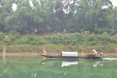 地方渔夫钓鱼与他的在Trang的小船一条河 免版税库存图片