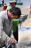 地方渔夫从他们的在Lagi海滩的捕鱼网去除鱼 免版税库存照片