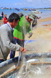 地方渔夫从他们的在Lagi海滩的捕鱼网去除鱼 免版税图库摄影