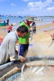 地方渔夫从他们的在Lagi海滩的捕鱼网去除鱼 库存图片