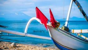 地方渔船有对圣巴厘岛的阿贡武尔卡诺岛的看法从努沙Penida海岛 部分盖由云彩 印度尼西亚 库存图片