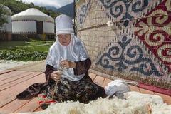 地方游牧礼服的哈萨克人年长夫人转动羊毛 免版税图库摄影