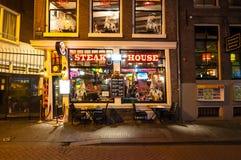 地方牛排餐厅和餐馆行在晚上在红灯区在阿姆斯特丹,荷兰 免版税库存图片