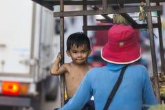 地方男孩游遍与她的他们的推车的母亲繁忙的s 免版税库存照片