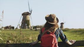 地方白种人女孩站立近的风车农场 帽子的村庄妇女有长的头发和红色背包的看  4K 股票视频