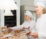 地方糖果店的微笑的女职工问候客户 库存照片