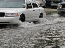 地方洪水-车辆驾驶通过水 库存照片
