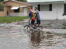 地方洪水-骑自行车通过水的男孩 库存照片
