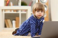 地板地毯用途膝上型计算机的逗人喜爱的小女孩 免版税库存照片