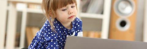 地板地毯用途膝上型计算机的逗人喜爱的小女孩 库存照片