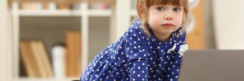 地板地毯用途膝上型计算机的逗人喜爱的小女孩 免版税库存图片