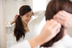 整洁地栓她的头发的美丽的亚裔妇女在镜子前面 免版税库存图片