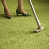地毯吸尘的妇女 免版税库存照片
