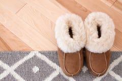 地毯和拖鞋在木地板上 免版税库存图片