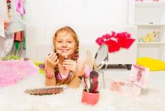 地毯和申请的嘴唇光泽美丽的女孩 库存照片