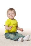 地毯的微笑的男婴 免版税库存图片