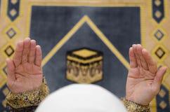 地毯的祈祷在传统佩带的衣裳,妇女的回教妇女的手在Hijab,圣堂地毯, 免版税图库摄影