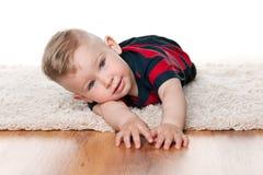 地毯的逗人喜爱的男婴 免版税库存图片