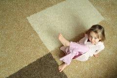 地毯逗人喜爱的女孩一点 图库摄影