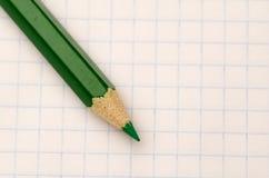 地点在笔记本板料的被削尖的铅笔 库存照片