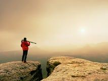 地点的艺术摄影师拍与照相机的照片在岩石峰顶  有雾的横向 免版税库存照片