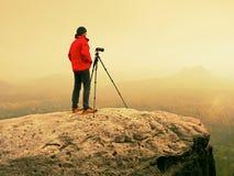 地点的艺术摄影师拍与照相机的照片在岩石峰顶  有雾的横向 免版税图库摄影