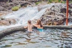 地热温泉 放松在温泉水池的母亲和儿子以瀑布为背景 图库摄影
