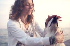 轻轻地爱抚她的狗的所有者 免版税图库摄影