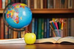 地球、组织者、一个苹果和一本开放书在桌上在背景图书馆 免版税库存照片