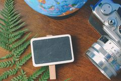 地球、葡萄酒照相机和标志布局在木桌上 免版税库存照片