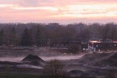 地球和大厦有薄雾的土墩反对树与橙色和桃红色天空在日落 免版税库存图片