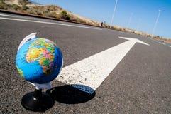 地球和箭头在沥青街道上对未来 免版税库存图片