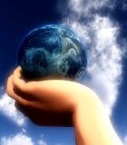 地球在手中在天空26前面 免版税库存图片