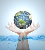 地球在手中在水 免版税库存图片