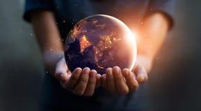 地球在晚上在人的手上举行 变褐环境叶子去去的绿色拥抱本质说明说法口号文本结构树的包括的日地球 免版税库存照片