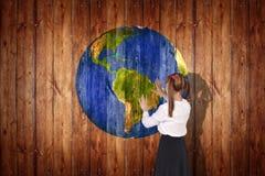 地球在木背景的球纹理 库存图片